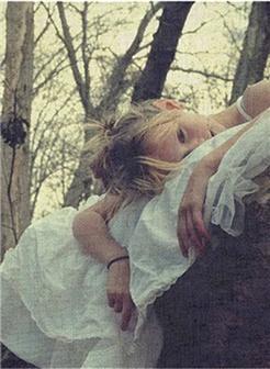 趴在枯树上的女生悲伤图片