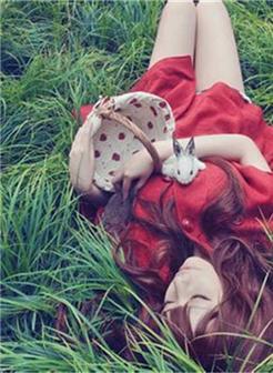 挽着花篮躺在草地闭上眼睛的女生