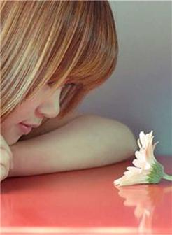注视着桌面的一朵花的女生图片