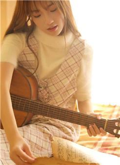 长发女孩抱着吉他暖色唯美照片