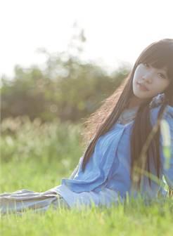躺坐在草地中的女孩,长焦镜头营造了浅景深,画面清新自然