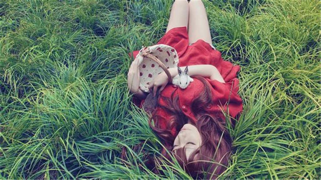 挽着花篮躺在草地闭上眼睛的女生(点击浏览下一张趣图)